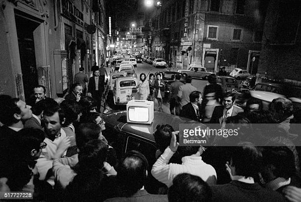 Crowd watches election results on portable TV atop a car in a Rome street Neofascists scored their greatest election triumph since World War II...
