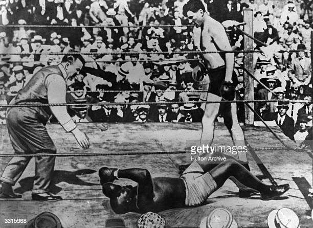 Jack Johnson of the USA is counted out by the referee after being knocked out in the 26th round by Jess Willard during their World Heavyweight title...
