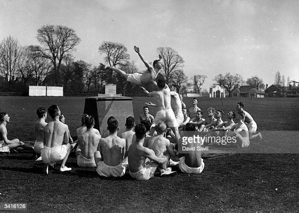 Students of the Physical Education Class at Loughborough College watching a demonstration of springing and diving over a box horse