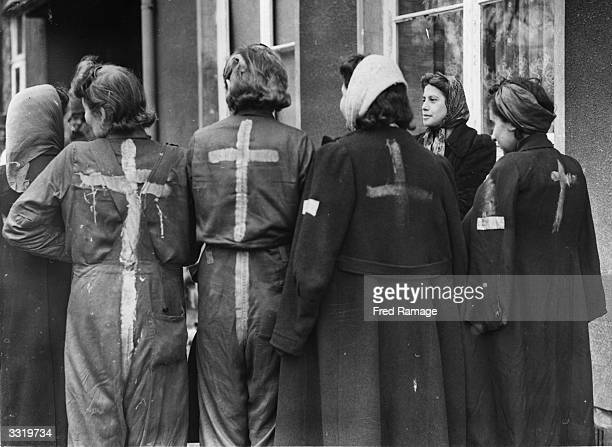 A group of liberated Jewish girls who were used as slaves in a munition factory at the Nazi camp in Kaunitz Germany wearing overalls and coats with a...