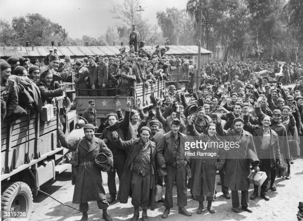British American and Allied prisoners of war cheer as their liberators the 9th Army move them out of the Nazi camp at Altengrabow Germany