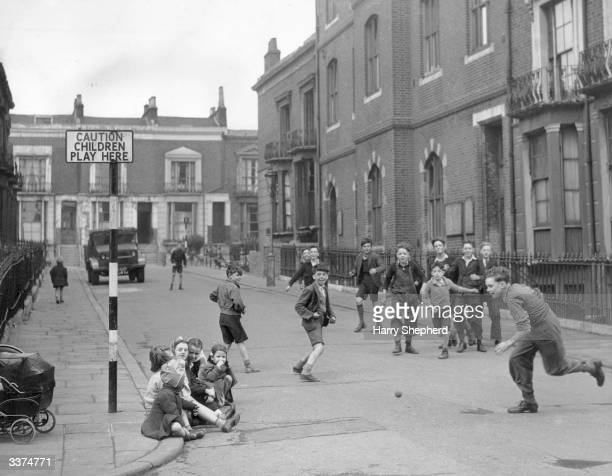 Children play unhindered in the street following the erection of a sign warning motorists that the street is now off limits except for access to...