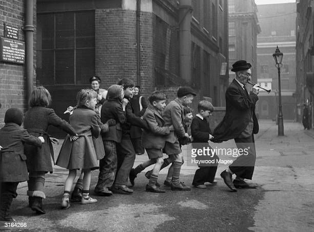 Jack Irving known as 'Charlie the Dancer' who has lived by busking in Central London for 40 years does a Pied Piper act for children in Covent Garden...