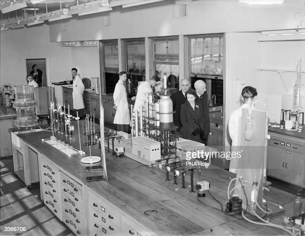Queen Elizabeth II accompanied by Lord Strathalmond chairman of the British Petroleum Company visits a chemical laboratory during her tour of the...