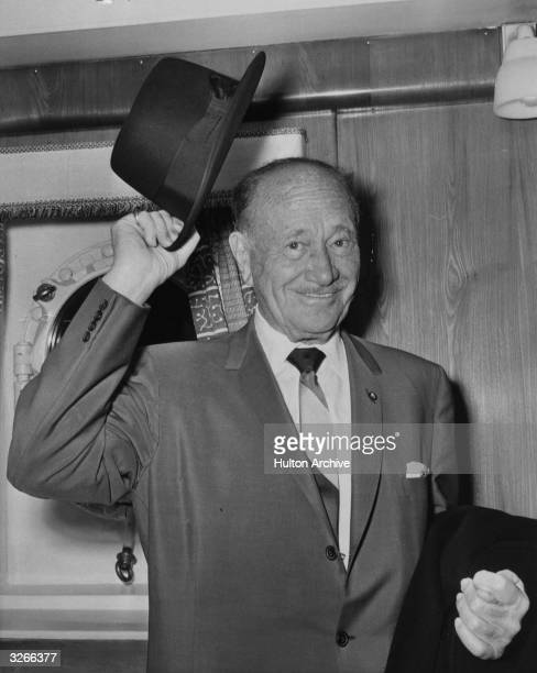 Conrad Hilton the Chairman and President of the eponymous hotel chain tips his hat