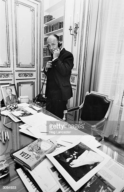 French fashion designer Pierre Balmain at work in his Parisian fashion house.