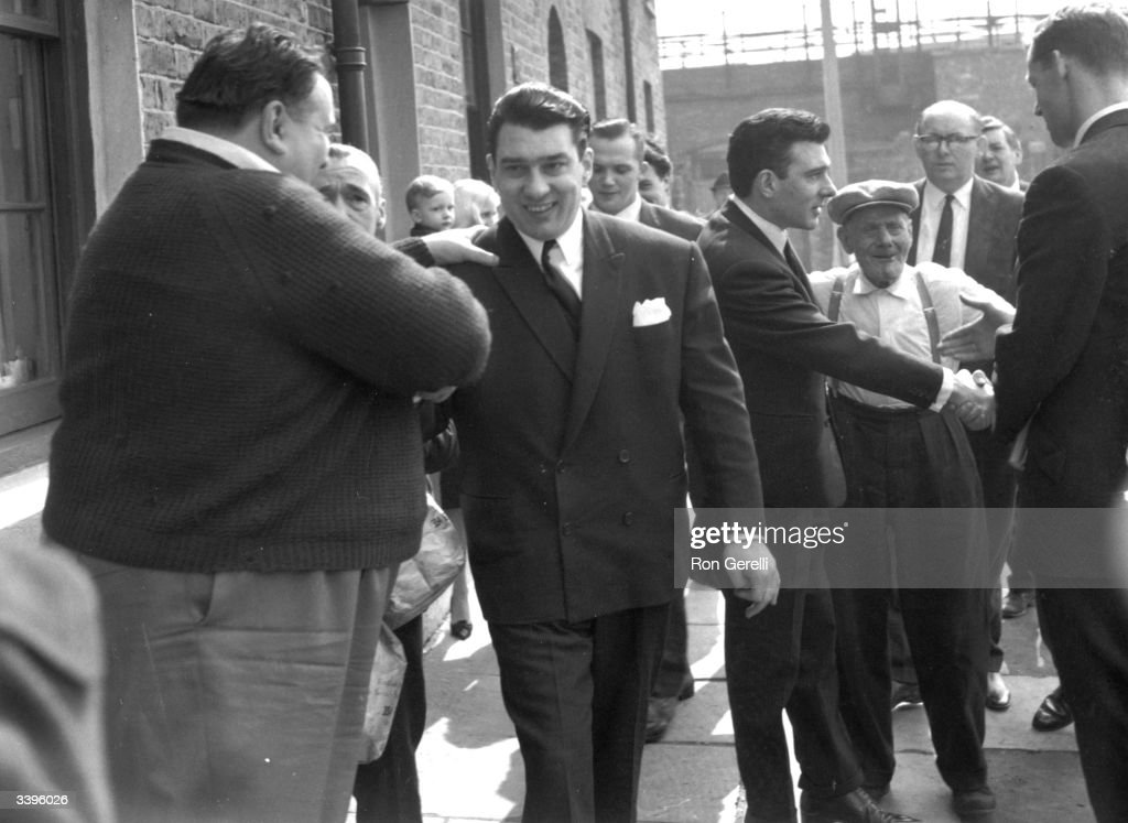 London gangsters Ronnie and Reggie Kray being welcomed home after being found not guilty on a menaces charge. They are with their grandfather, Jimmy Lee.