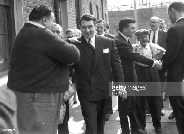 London gangsters Ronnie and Reggie Kray being welcomed home after being found not guilty on a menaces charge They are with their grandfather Jimmy Lee