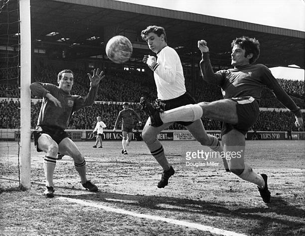 Bobby Tambling of Chelsea tries a shot at goal from an acute angle as Latcham of Burnley attempts to block him and goalkeeper Thomson covers his near...