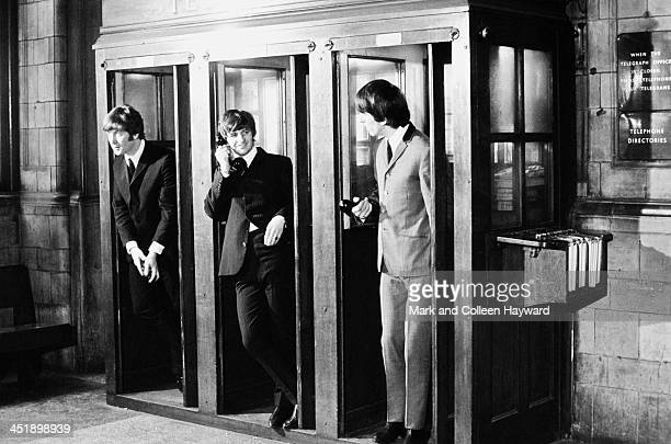 From left to right John Lennon Ringo Starr and George Harrison from The Beatles pose in the telephone booths at Marylebone Station in London during...