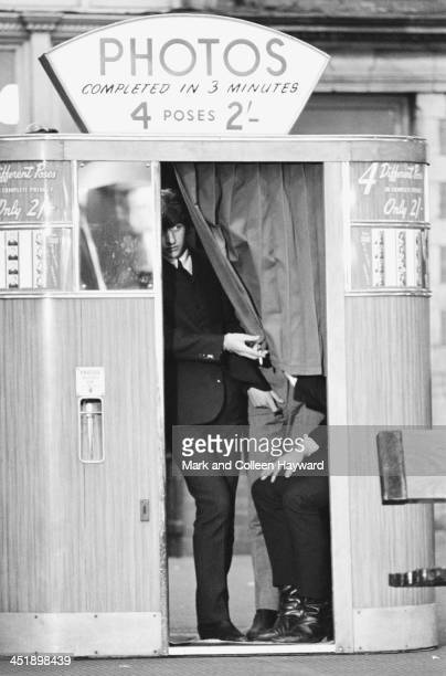 Ringo Starr peaks out from behind the curtain of a photo booth at Marylebone Station in London during the filming of 'A Hard Day's Night' on 5th...