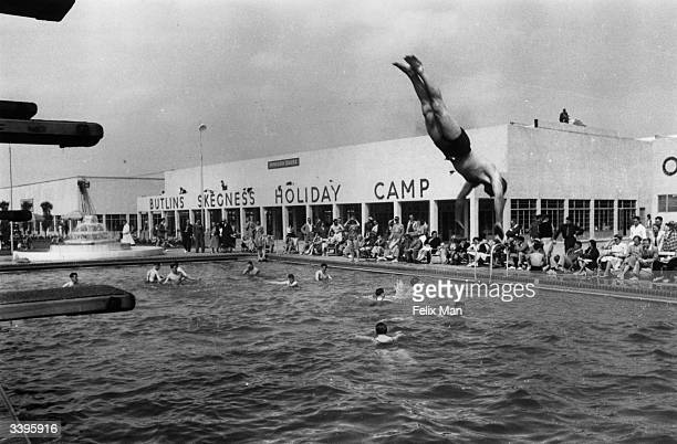 A swimmer diving into a busy swimming pool at Butlin's Holiday Camp Skegness Lincolnshire Original Publication Picture Post 193 Holiday Camp pub 1939