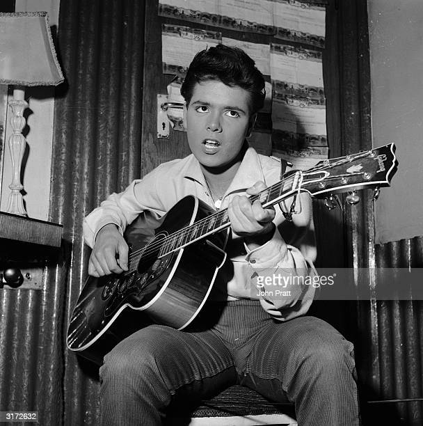 English pop star Cliff Richard strums a tune on his trusty guitar before a concert