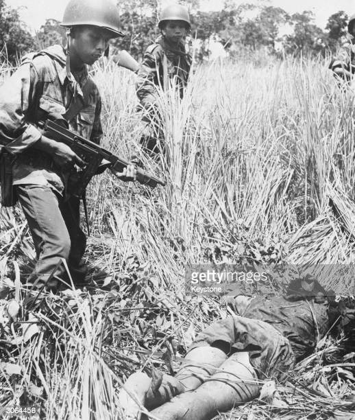 A Viet Cong guerilla is gunned down and killed by South Vietnam troops during the Vietnam War