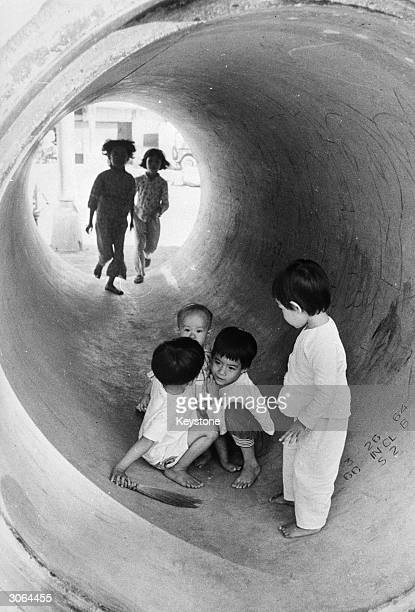 Vietnamese children at play inside a giant concrete pipe in Saigon during the War in Vietnam