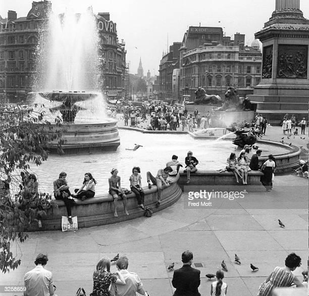 Tourists relax in Trafalgar Square London