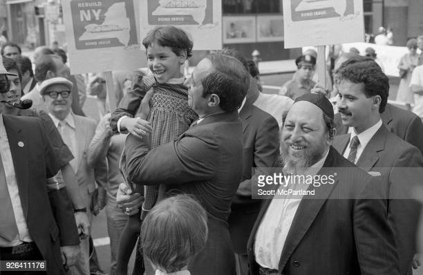 New York Governor Mario Cuomo holds a young girl in his arms as he glad hands people on the streets of New York City Governor Cuomo is pushing the...