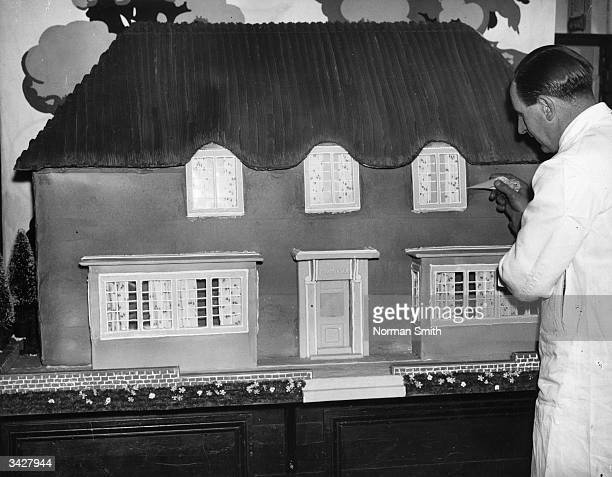 A novel Christmas cake in the form of Princess Elizabeth's Welsh cottage being worked on by Mr F C Buck a confectioner of Upton Park London
