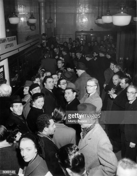 Eager customers crowd the post office in London's Leicester Square at midnight hoping to obtain 'first day covers' the first stamps issued during the...