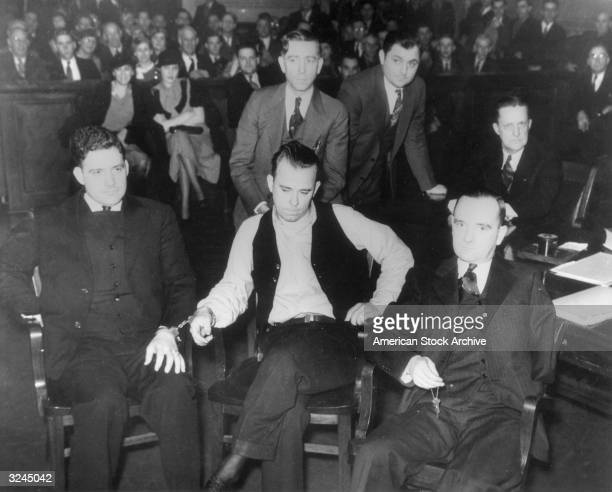 American criminal John Dillinger sits handcuffed to Deputy Chief Carroll Holby beside his attorney Joseph Ryan while on trial in Crown Point Indiana