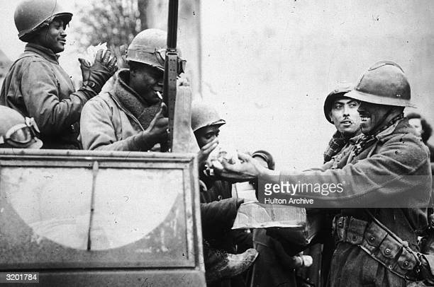 French soldiers distribute handfuls of candy to US soldiers in a jeep in celebration of the closing of the Colmar Pocket Battle Colmar France World...