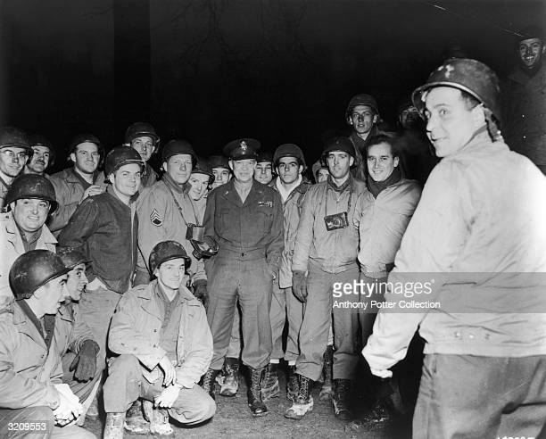 Full-length image of General Dwight D Eisenhower, Supreme Allied Commander, standing outdoors amongst a group of soldiers at night, World War II.