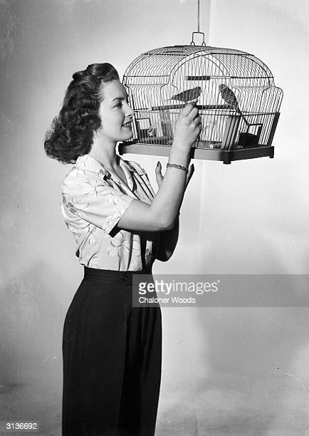 British actress Patricia Roc plays with a pair of caged birds