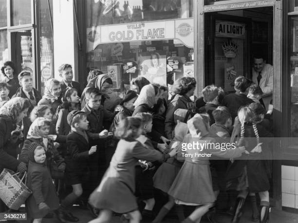 A crowd of children rush to get into a sweetshop in north Acton as it opens its doors on the day sweet rationing ended