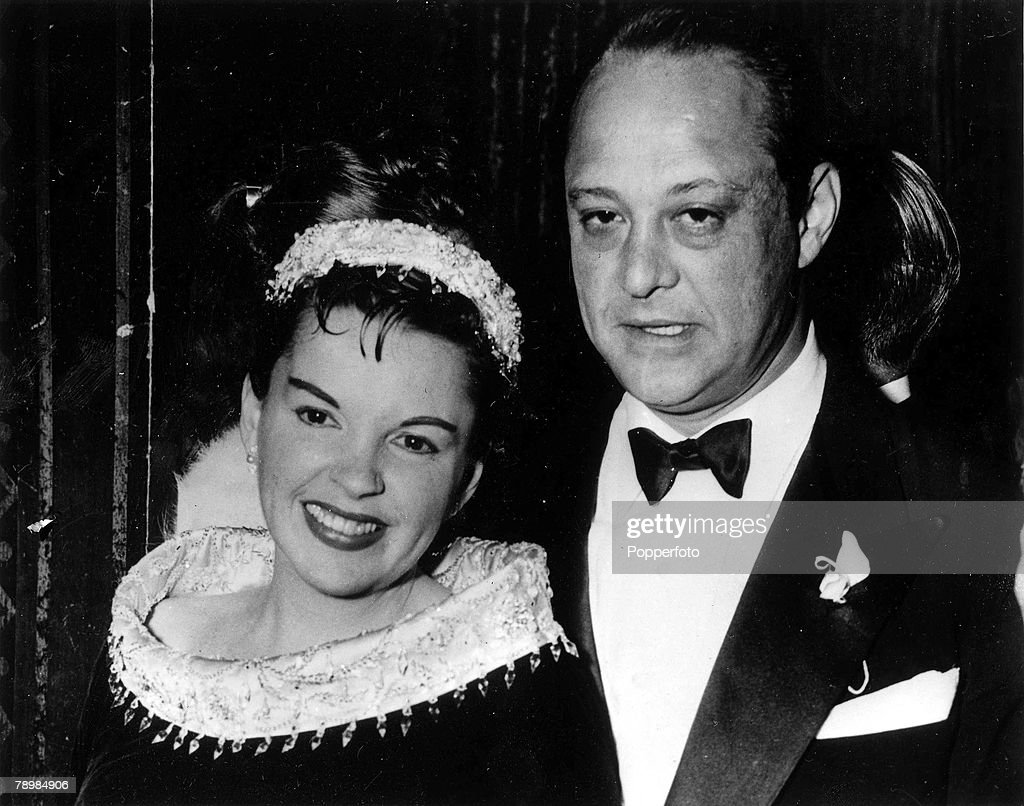 """5th February 1956. Santa Monica, California. Singing film star Judy Garland arrives at the Hollywood premiere of her film """"A Star is Born"""" with third husband Sid Luft - against whom she filed for divorce, charging extreme cruelty. : News Photo"""