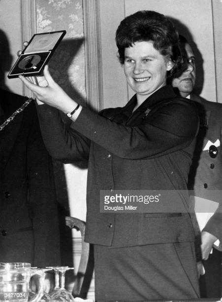 Russian astronaut Valentina Tereshkova holds up a gold medal presented to her by the British Interplanetary Society on her visit to London The medal...