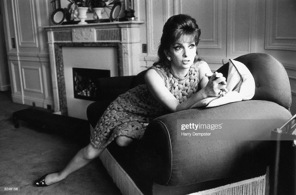 Italian film star Gina Lollobrigida reclines on hotel sofa during a visit to London.