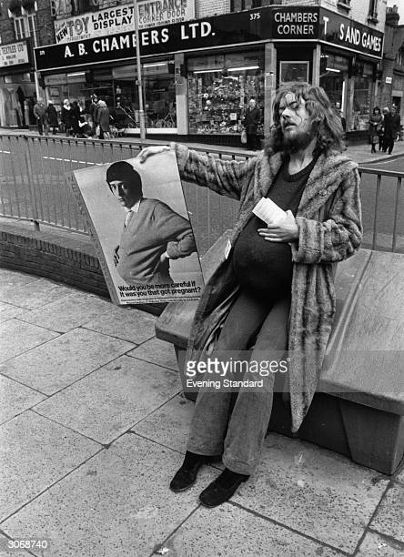 A bearded young man with a fake pregnancy bulge stands in a busy street holding a Newham Birth Control Campaign poster The poster also depicts a...