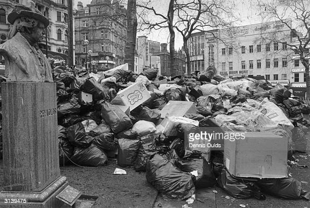 Rubbish bags piled high round the statue of Reynolds in Leicester Square as dustman strike for an increase in pay