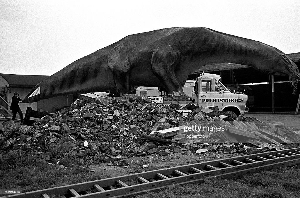 """5th February, 1973, A boy grabs the tail of a 45 foot long Cetiosaurus dinosaur which is made of tubular steel and covered with paper, wire mesh and concrete, The """" Monster """" pictured at Canvey Island, Essex is to be exhibited in Scotland : News Photo"""