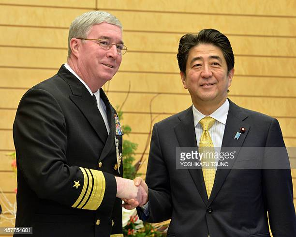 US 5th Fleet commander vice admiral John Miller shakes hands with Japanese Prime Minister Shinzo Abe prior to their talks at Abe's office in Tokyo on...