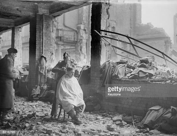 Using a bombed building in London as a temporary barber's shop a member of the Pioneer Corps gets a short back and sides from a mate