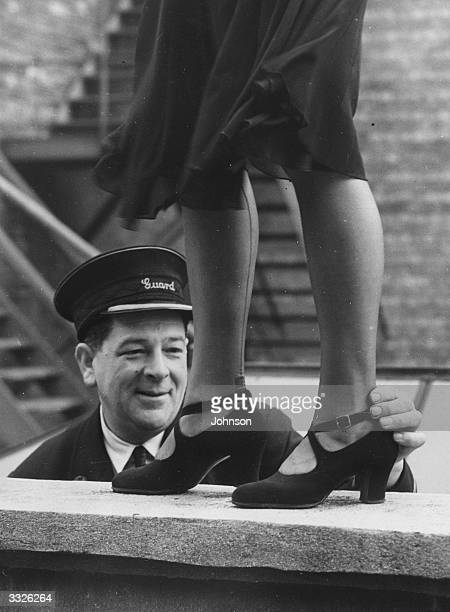 Railway guard George Wiltshire judge of an ankle competition organised by the Women's Section of the British Railways Social Club at Oxford with the...