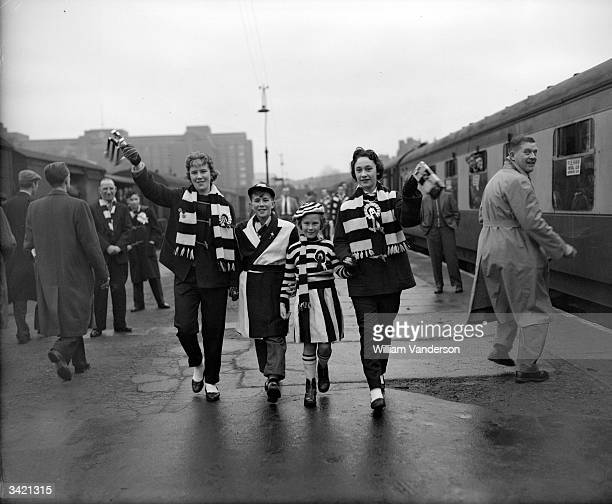 Fulham Football Club fans wear their team colours at Addison Road Station, where they are catching a special Supporters Club train to travel to an FA...