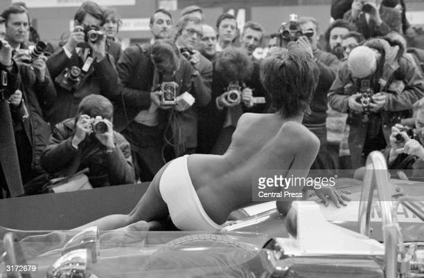 Camera men crowd around a topless model posing on one of the exhibits at the Racing Car Show at Olympia London