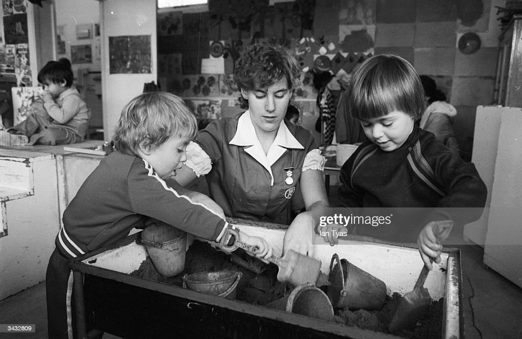 A trainee nanny at the Princess Christian College in Manchester supervises two children at the sandpit.
