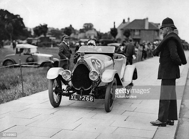 A policeman watches as a contestant takes part in speed trials driving her Bugatti on the pavement