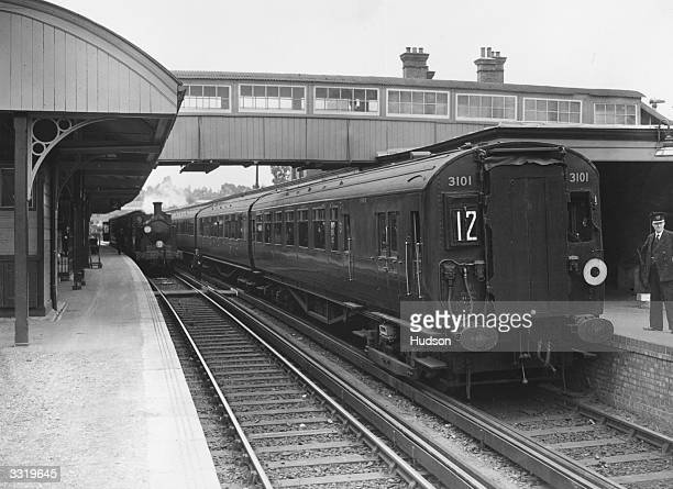 New electric train and a traditional steam train at Aldershot station. The electric train runs for 22 miles between Woking and Aldershot, Surrey, and...
