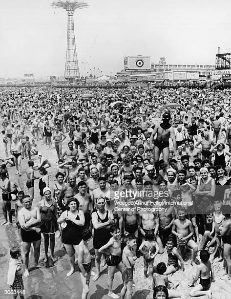 A crowded beach of New York's Coney Island at noon on a saturday The masked man calls himself 'Spider' and claims that he likes to frighten people...