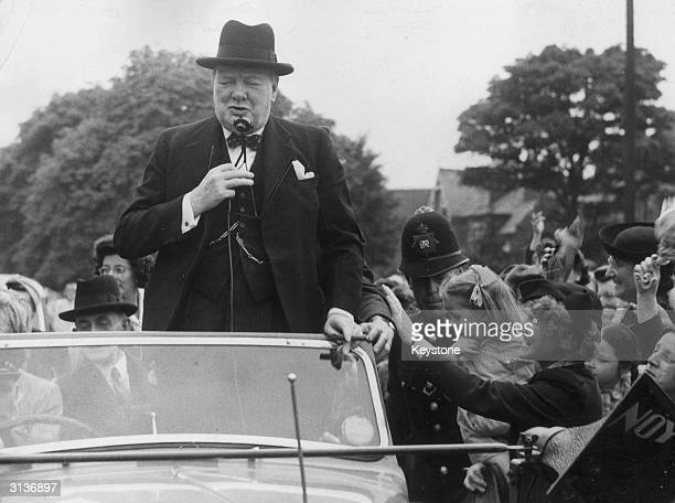 The British statesman Sir Winston Leonard Spencer Churchill greets the crowd at Woodford during his tour of London.