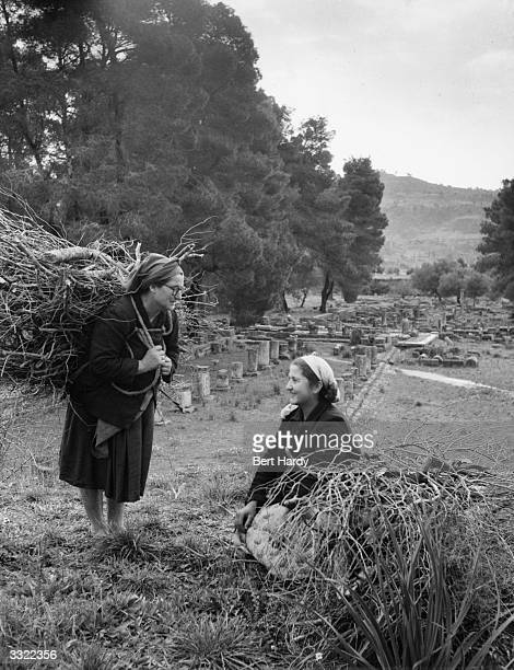 Two women gathering firewood near the ruins of ancient Olympia in Greece Behind them are the remains of the gymnasium Original Publication Picture...