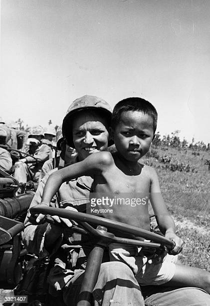 A local boy sits on the lap of a soldier of the 27th Wolfhound Division of the US Army in north Thailand The soldiers are there to learn guerilla...