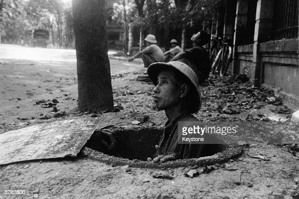 A member of the public seeks refuge in an airraid shelter in Hanoi while American bombers raid the city