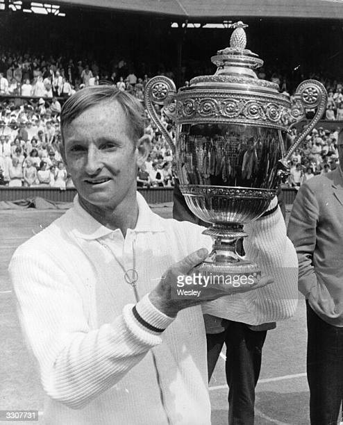 Australian tennis player Rod Laver lifts the trophy after beating Tony Roche of Australia in the men's singles final at Wimbledon