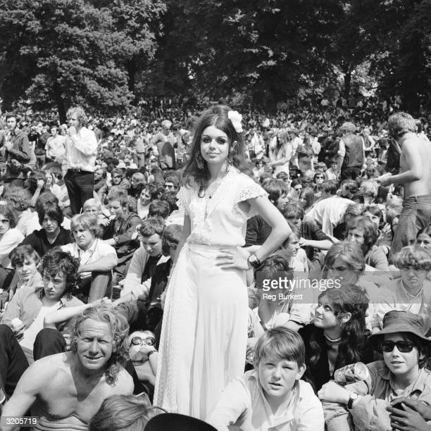 A woman standing among the crowds gathered in Hyde Park to see the Rolling Stones in concert