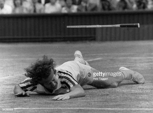 American tennis player John McEnroe falls to the ground in defeat and is followed by his racquet during the men's singles final of the Wimbledon Lawn...